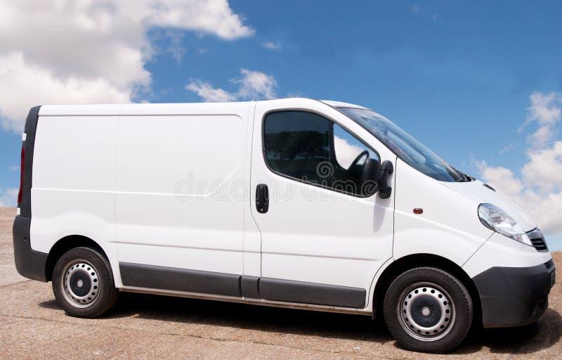 Small white Van. Small white trade-van parked on red forecourt stock photo