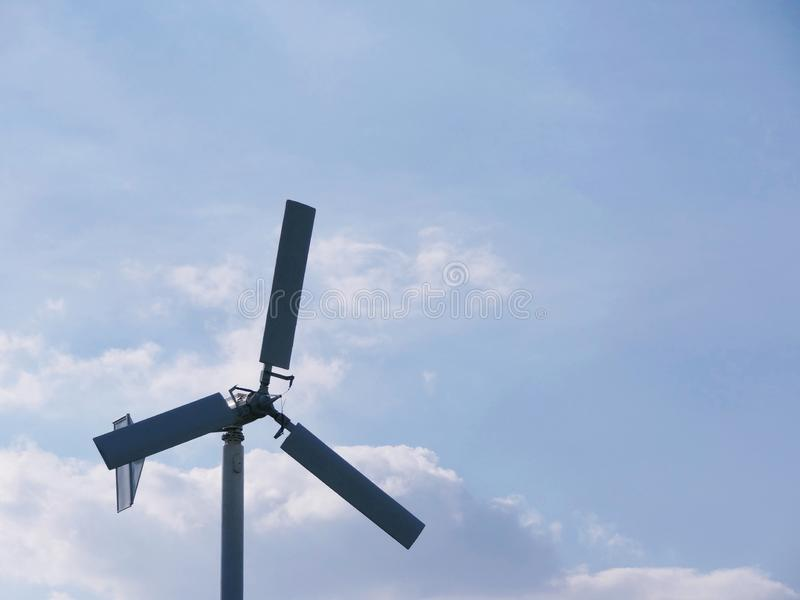 Small white wind turbine, windmill alternative Green clean energy against blue sky stock images