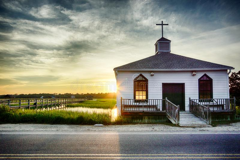 Small white wooden chapel on the water on the coast during a colorful summer sunset stock images