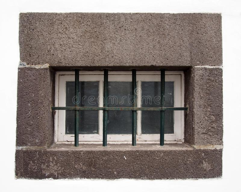 Small white wooden window with glass panes covered by steel bars in a large grey stone frame on a white wall royalty free stock images