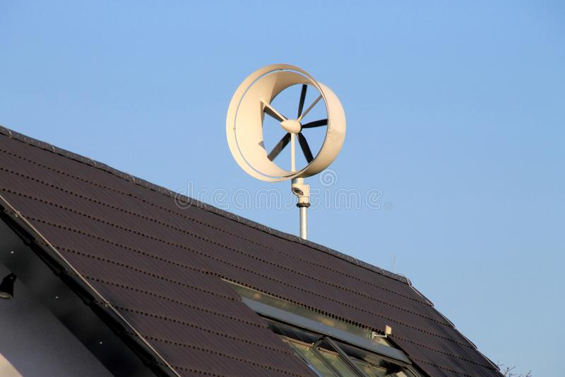 Small wind turbine on roof for private using. Single small wind turbine on roof for private using stock image