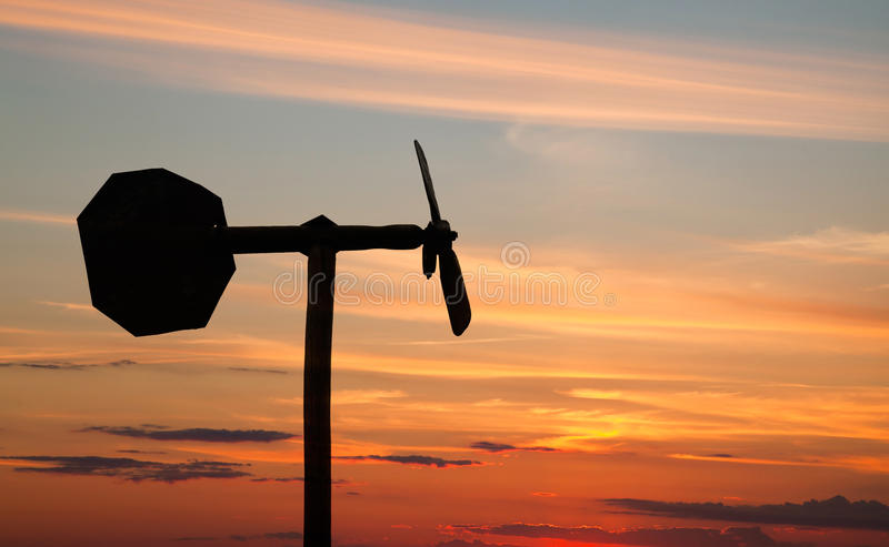 Small windmill style weather vane silhouette. Above orange sunset sky stock photo