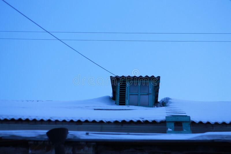 Blue skylight at dusk in the city. Small window on the snowy roof of a house at dusk. Photo taken in Krasnoyarsk, Russian Federation stock photo