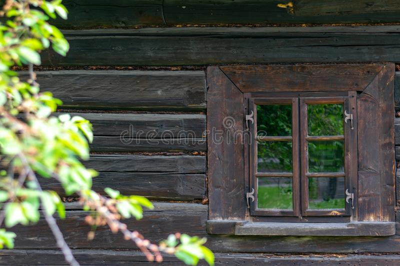 A small window in the wall of an old wooden house royalty free stock image