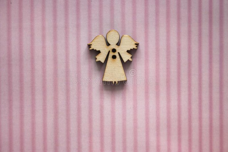 Small wooden angel figure on pink striped background. Greeting card design. Gift and present concept. Birthday background. Angel and newborn baby concept stock photos