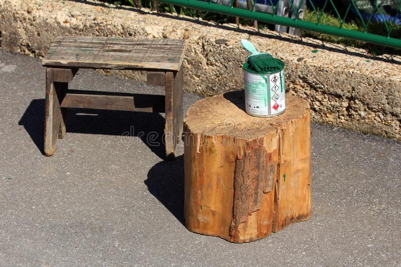 Small wooden bench next to cut down large tree stump with open paint can and brush used to paint family house fence. On warm sunny spring day stock images