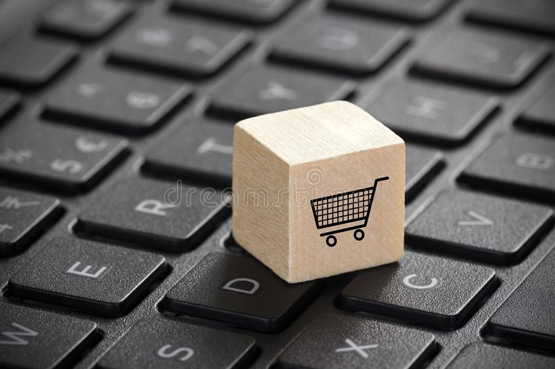 Wooden block with shopping cart graphic on laptop keyboard. Online shopping concept. royalty free stock photo