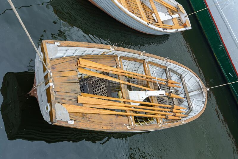 A small wooden boat with oars moored. At the pier stock photo