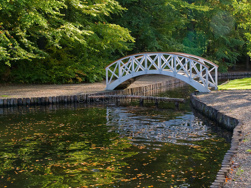 Small wooden bridge over river. Beautiful small wooden footbridge in Tivoli Arhus Denmark royalty free stock photography