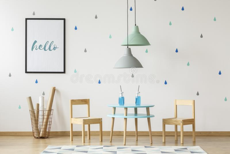 Small wooden chairs and table set for kids and mock-up poster on stock photography