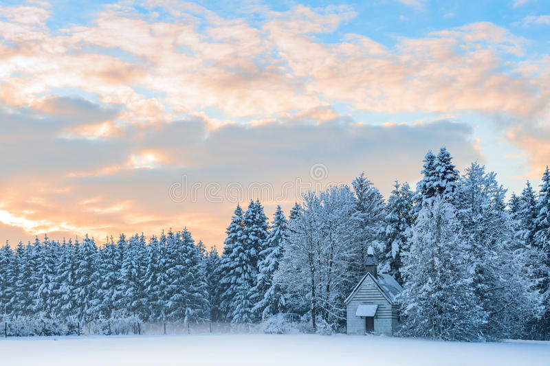 Small wooden chapel in snowbound frosty forest under sunrise sky royalty free stock photography