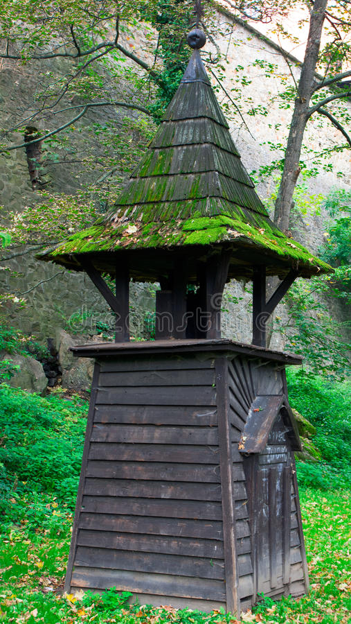 Small wooden chapel. Standing under the old city walls in the present park. Old stone walls are with opening to put a canon there. The roof of the chapel is royalty free stock photography
