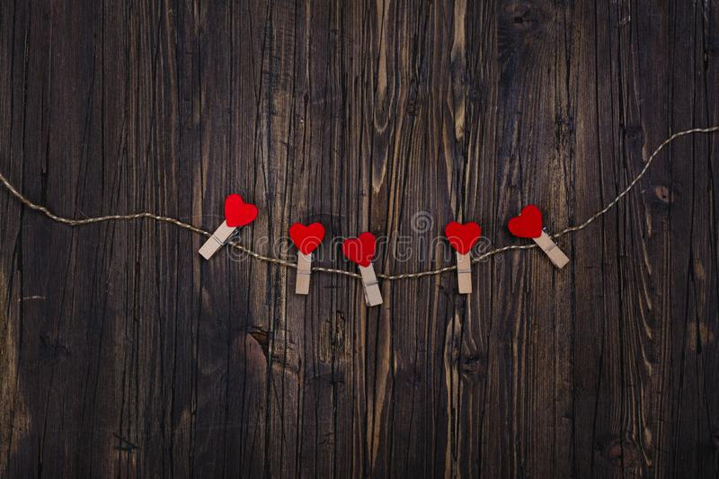 Small wooden clothespin with red hearts hanging on rope stock image