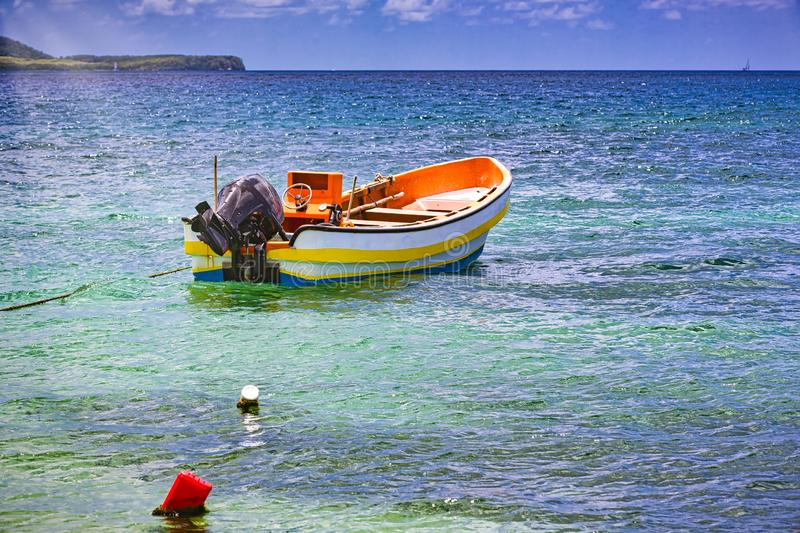 Small wooden colorful boat on clear water ocean stock photography