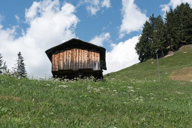 Small wooden cottage in midst an idyllic mountain landscape in Switzerland royalty free stock image