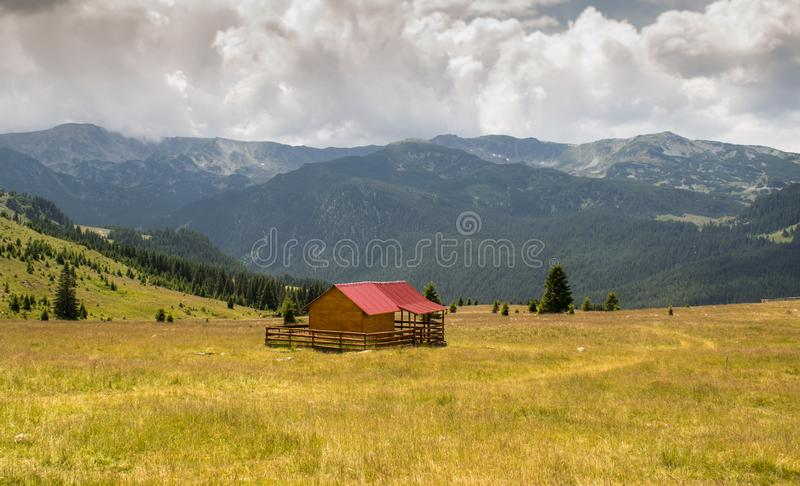 A small wooden cottage situated in a dream landscape, somewhere in the heart of the mountains. A beautiful green plain with fir. Trees and beautiful mountains royalty free stock image