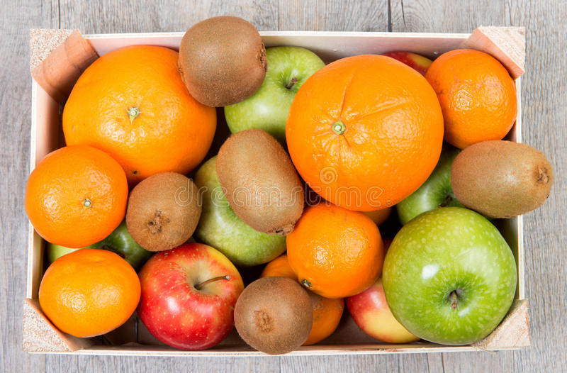 A small wooden crate with fruits. A small wooden crate with several fruits stock photo