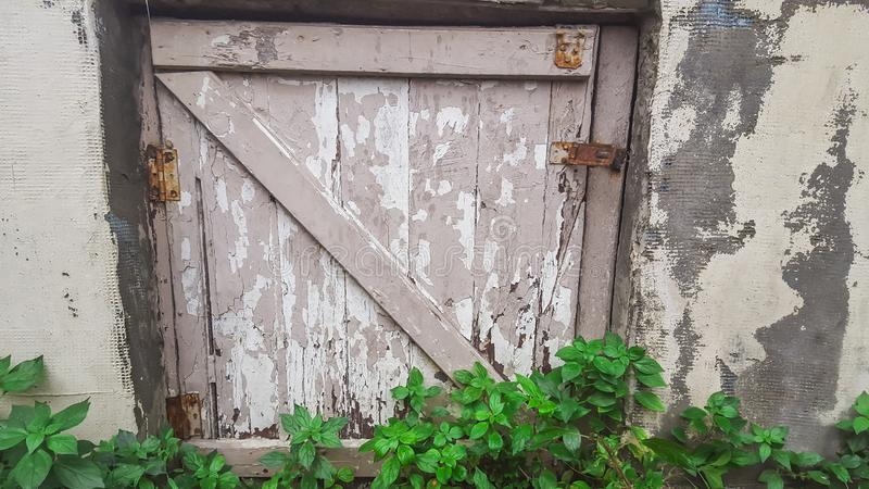 Small wooden door with lock in stone wall royalty free stock photography