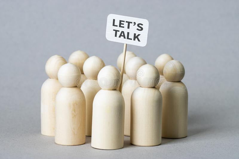 Small wooden figures with a `Let`s Talk` poster stock image
