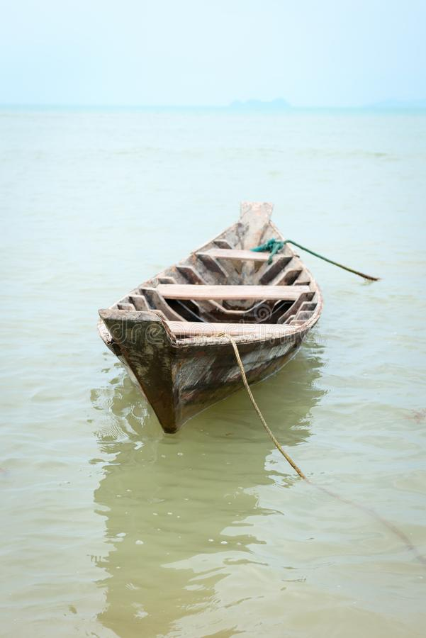 Small wooden fishing boat. In calm water royalty free stock photo
