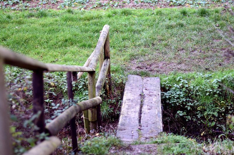 Small wooden foot bridge with railing over ditch in a field in England. Small wooden foot bridge with railing over ditch in arable field in England. Viewer is royalty free stock image