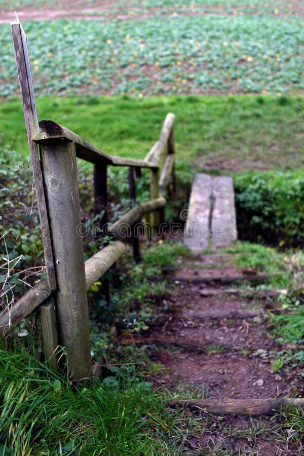 Small wooden foot bridge with railing over ditch in field in England. Small wooden foot bridge with railing over ditch in arable field in England. Viewer is royalty free stock photos