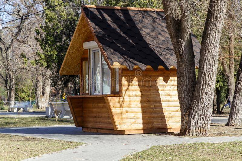 The small wooden house among big trees. VOLGOGRAD, RUSSIA - April 11, 2018: The small wooden house among trees, in the morning stock photography