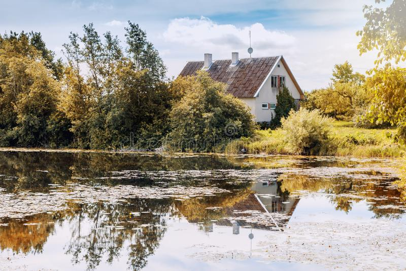 A small wooden house on the edge of a forest and on the shore of stock photo