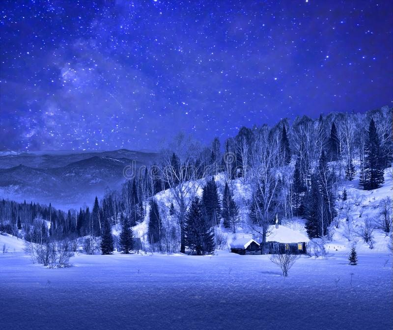 Small wooden house in a night winter mountain landscape stock photos