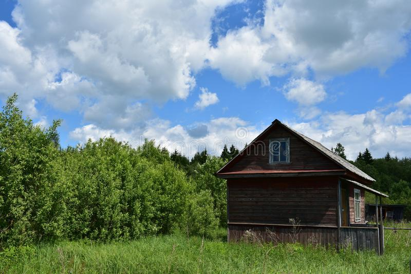 A small wooden house with a porch on the edge of a thick forest, sky clouds royalty free stock photography