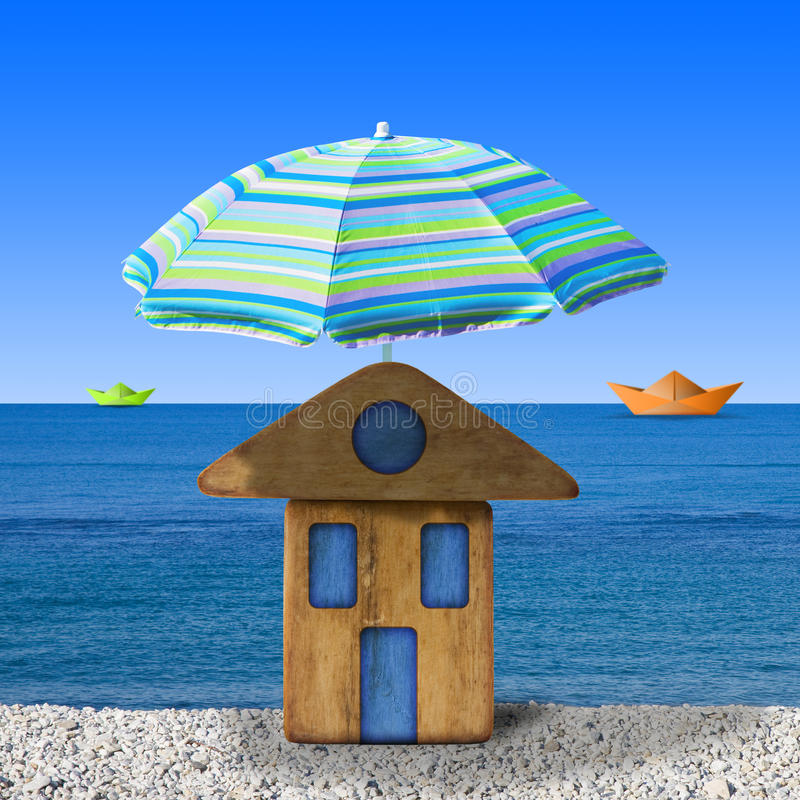 Small wooden house at seaside with umbrella beach - concept image.  royalty free stock image