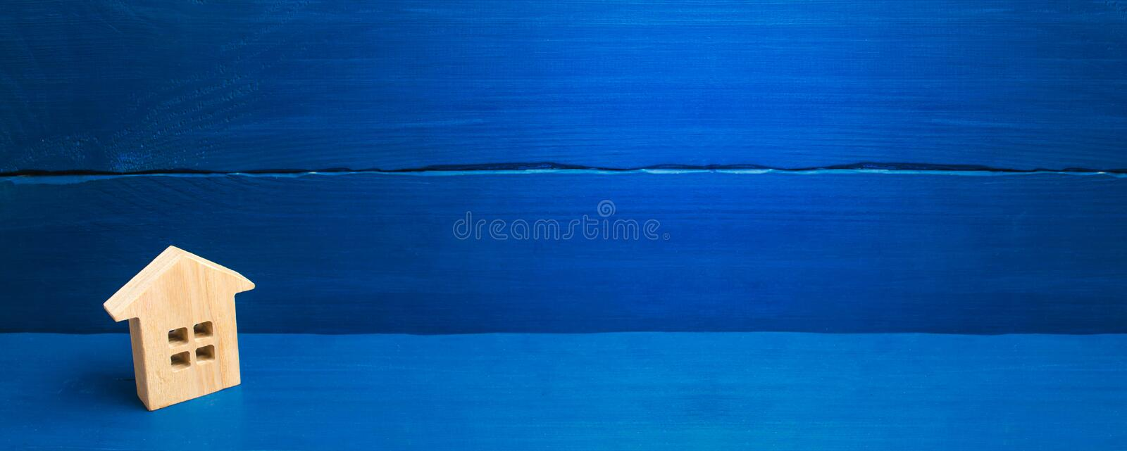 A small wooden house stands on a blue background. The concept of buying and selling real estate, renting. Search for a house. Affordable housing, credit and royalty free stock photography