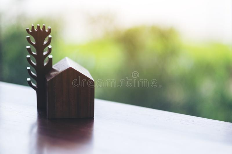 A wooden house and tree model on the table. A small wooden house and tree model on the table stock images