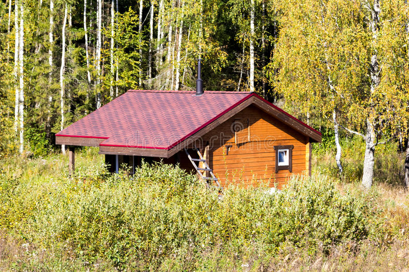 Small wooden house among trees and bushes. Small wooden house among the trees and bushes stock photo