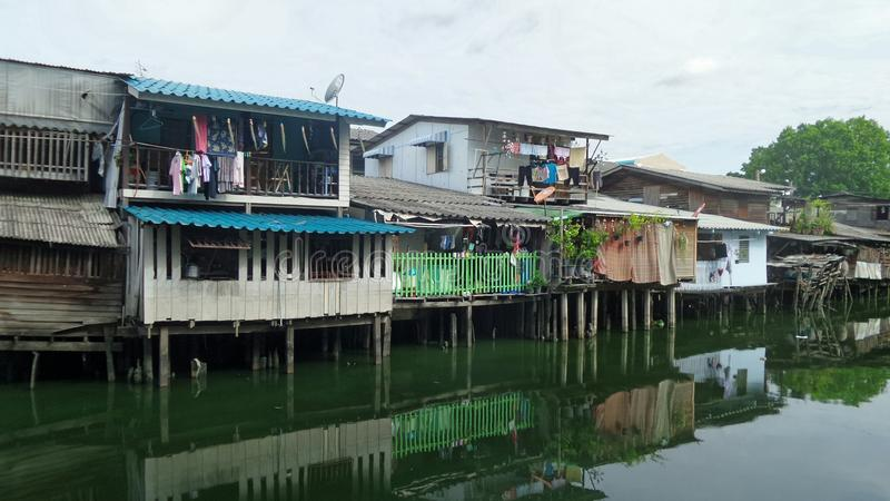 Small wooden houses on canal bank in the city. Canal front life community in busy city in Thailand. Thais people usually built their homes along waterways and stock photos