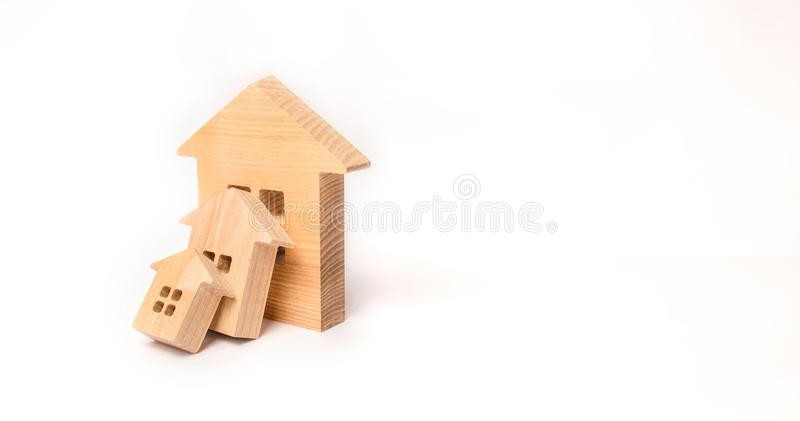 Small wooden houses fall on the big house as a domino. The concept of buying real estate. Insurance and investment risk. Falling. Prices in the real estate royalty free stock image