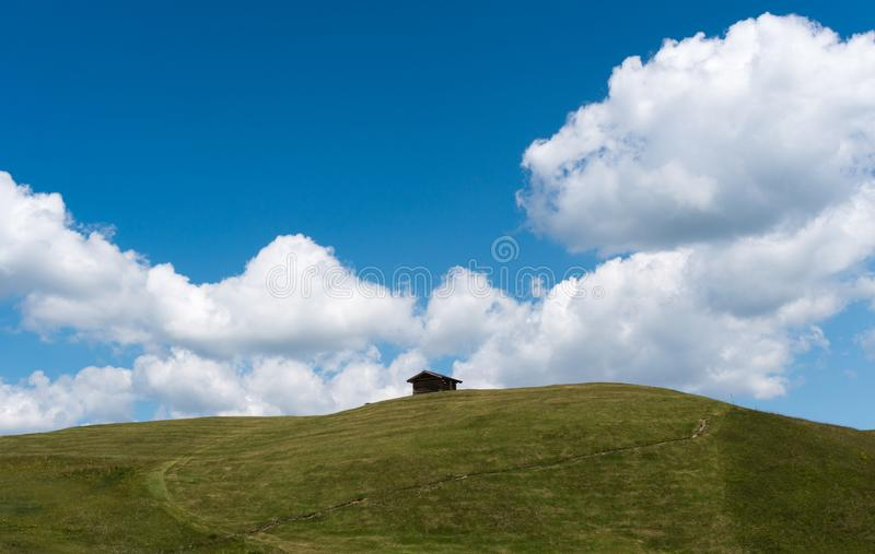 Small wooden hut on a grassy alpine hill and ridge under a blue sky with white clouds in the Swiss Alps royalty free stock image
