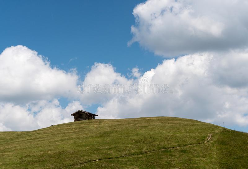 Small wooden hut on a grassy alpine hill and ridge under a blue sky with white clouds in the Swiss Alps royalty free stock photo