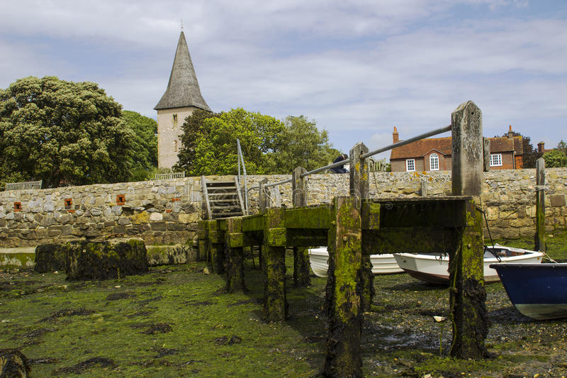 A small wooden jetty covered with barnacles and seaweed in the harbour at Bosham village in West sussex in the South of England royalty free stock photography