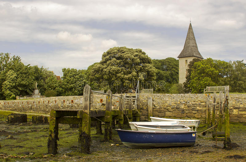 A small wooden jetty covered with barnacles and seaweed in the harbour at Bosham village in West sussex in the South of England royalty free stock photos