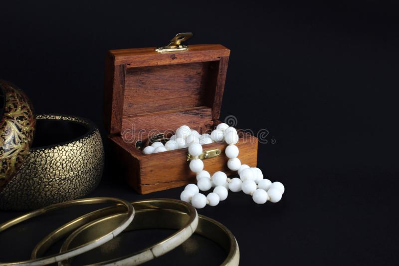 Wooden jewelry box. A small wooden jewelry box with pearls and bracelet on black background royalty free stock image