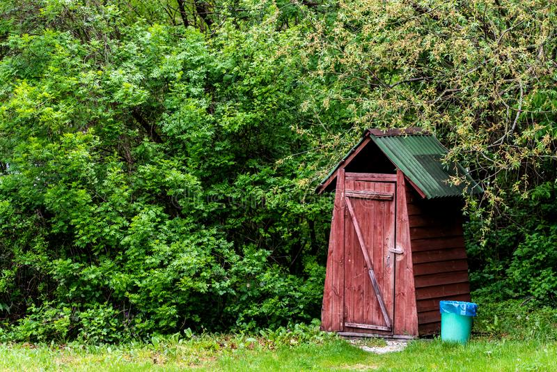 Small wooden outdoors toilet in summer royalty free stock image
