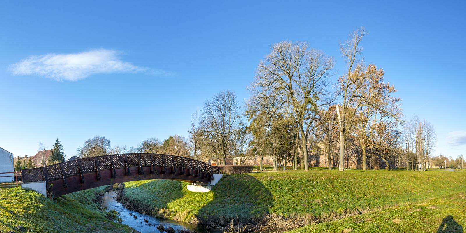 A small wooden pedestrian bridge leading to historical medieval Zrinyi Castle in a nice sunny winter day, Szigetvar, Hungary royalty free stock photo