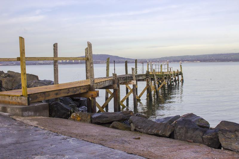 A small wooden pier on The Esplanade at Holywood County Down. A small wooden pier used by the local yaucht club on The Esplanade at Holywood County Down. Belfast royalty free stock photography