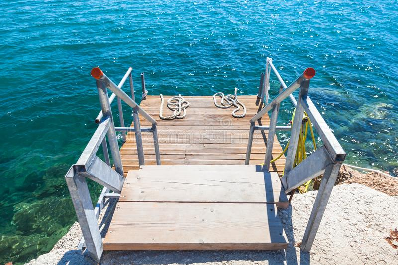 Small wooden pier with metal railings royalty free stock photos