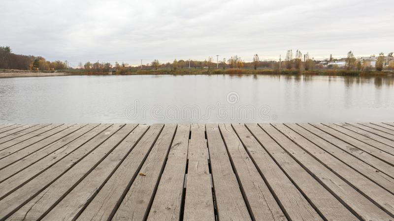 A small wooden pier on a quiet lake in the autumn foggy morning.  stock photo