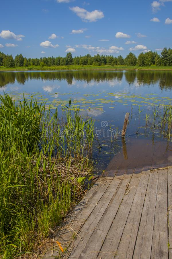 A small wooden pier on the river stock image