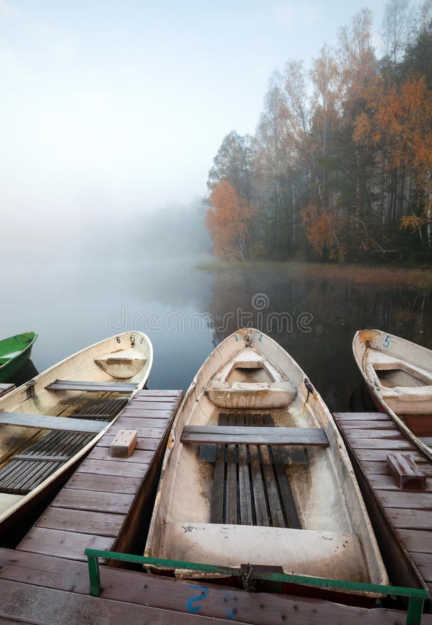 Small wooden pier with rowboats on still lake stock image