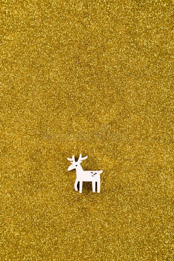 Wooden reindeer Christmas decoration on golden glitter background royalty free stock images