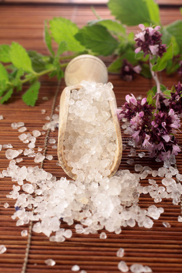 Small wooden shovel with bath salt. And herbs royalty free stock photo